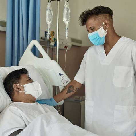Masked and gloved male nurse reassures a masked male patient in hospital bed.