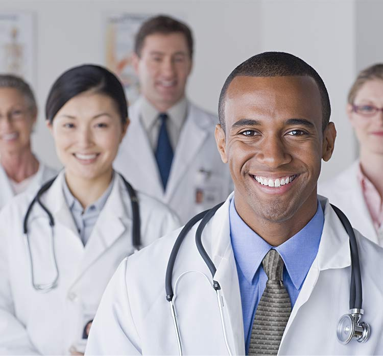 A photo of several doctors of different backgrounds smiling into the camera.