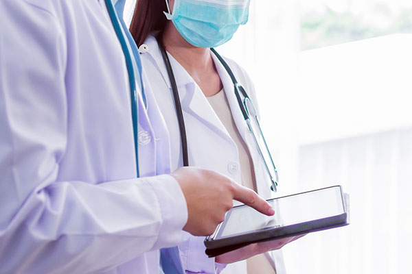 Two healthcare professionals in white coats looking at data on a digital tablet.