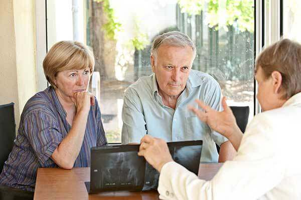 Concerned older couple looks at Xrays with a doctor
