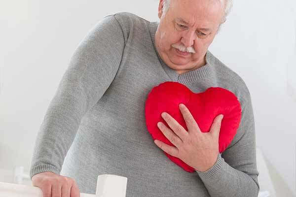 Older senior clutches heart-shaped pillow to his chest as if he has angina
