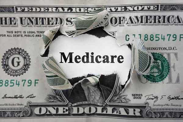 Illustration of the word Medicare ripping through a $1 bill