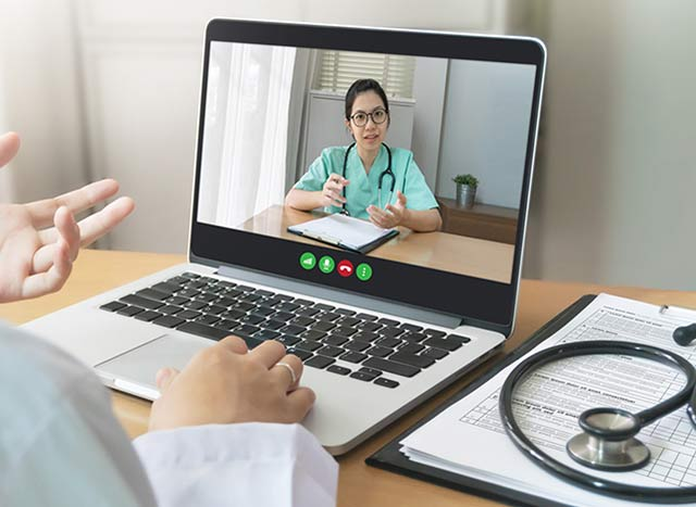 Two female doctors discuss medicine via teleconference on computer.